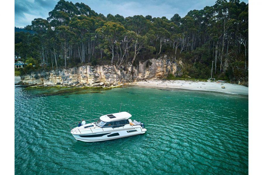 Jeanneau Merry Fisher 1095 wheelhouse fishing boat - high view near beautiful beach
